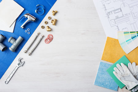 Plumber's work table banner with work tools, faucet, tiles and color swatches, top view, copy space at center Archivio Fotografico