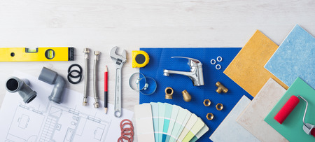 Plumber's work table banner with work tools, faucet, tiles and color swatches, top view Archivio Fotografico