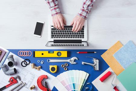 다음 배관 작업 도구, 타일 및 견본, 온라인 예약 및 홈 배관공 서비스에 랩톱을 사용하는 남성의 손에