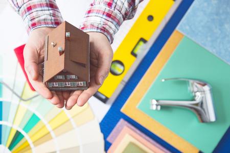 plumber: El seguro de hogar, reparación y servicio de decoración concepto con las manos ahuecadas que sostienen una casa modelo y el grifo, muestras de color y herramientas de trabajo