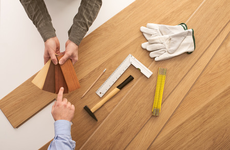 Carpenter showing some wooden baseboard swatches to a customer and choosing a color, flooring installation and work tools on background