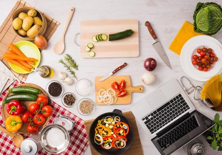 クリエイティブなベジタリアン キッチンには調理器具、新鮮な野菜と木製のテーブル、トップ ビューでのノート パソコン