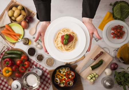 Handen van professionele chef-kok koken van pasta op een houten werkblad met groenten, voedselingrediënten en gebruiksvoorwerpen, bovenaanzicht