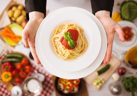 Hände professioneller Küchenchefs Kochen von Nudeln auf einem Holzarbeitsplatte mit Gemüse, Lebensmittelzutaten und Utensilien, Ansicht von oben Standard-Bild