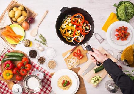 utensilios de cocina: Cocinero profesional freír las verduras frescas en rodajas en una sartén antiadherente manos cerca, ingredientes de alimentos y utensilios de cocina o Foto de archivo