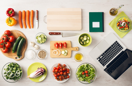 food on table: Vegetariana cucina creativa a casa con utensili da cucina, ingredienti alimentari e verdure fresche su un tavolo di legno, vista dall'alto Archivio Fotografico