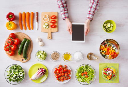 Mans hand cooking at home with touch screen tablet, fresh vegetables and kitchen utensils all around, top view Stock Photo