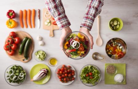 ensalada: Hombre que sostiene un taz�n de ensalada fresca con verduras en rodajas primas, manos close up vista superior, ingredientes y utensilios Foto de archivo