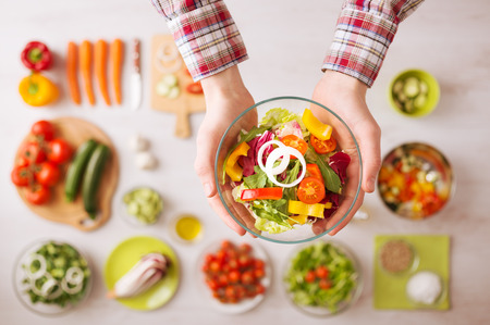 Man holding a fresh garden salad bowl with raw sliced vegetables, hands close up top view, ingredients and utensils