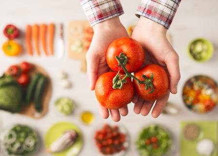 �cooking: Hombre que sostiene jugosos tomates frescos manos se cierran para arriba, verduras e ingredientes alimentarios, vista desde arriba