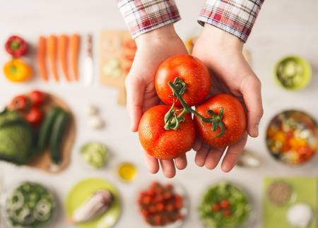 vegetarian food: Man holding fresh juicy tomatoes hands close up, vegetables and food ingredients, top view