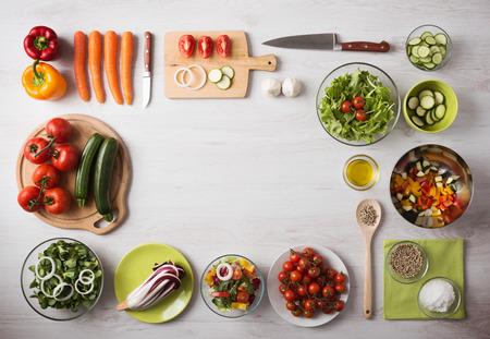 utencilios de cocina: Concepto de alimentación saludable con verduras frescas y ensaladeras sobre encimera de cocina de madera, espacio de la copia en el centro, vista desde arriba Foto de archivo