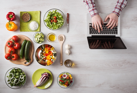 Man in the kitchen searching for recipes on his laptop with food ingredients and fresh vegetables on the left, top view