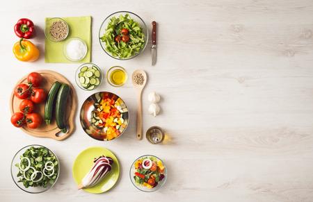 Gezond eten concept met verse groenten en salade kommen op keuken houten werkblad, kopieer de ruimte aan de rechterkant, bovenaanzicht