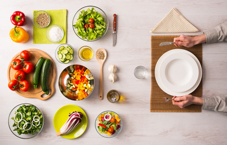 food ingredient: Healthy vegetarian meal concept with table set, hands holding fork and knife and fresh raw vegetables Stock Photo
