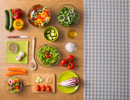 Healthy fresh vegetarian food on kitchen table with checked tablecloth on the right, top view Stockfoto