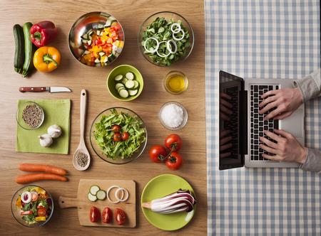 오른쪽에 노트북에 입력하는 손으로 식탁에 집에서 채식 건강 음식 준비, 상위 뷰