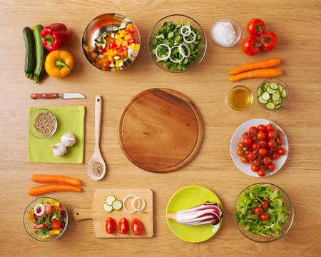 to lunch: Cocina vegetariana creativa en concepto de hogar con verduras frescas picadas saludables, ensaladas y utensilios de cocina de madera, vista desde arriba, con copia espacio