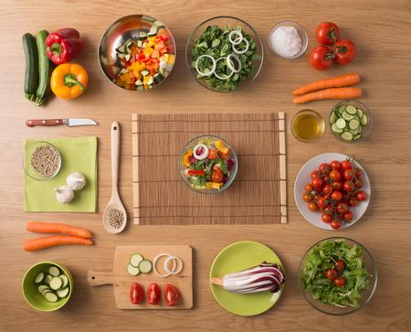 ensalada: Cocina vegetariana creativa en concepto de hogar con verduras frescas picadas saludables, ensaladas y utensilios de cocina de madera, vista desde arriba, con copia espacio