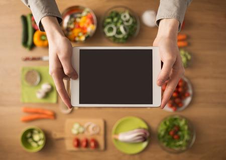 新鮮な野菜や台所用品のデジタル タッチ スクリーン タブレットを保持している手