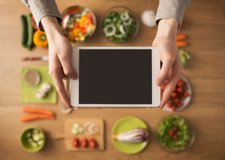 Hands holding a digital touch screen tablet with fresh vegetables and kitchen utensils Stockfoto