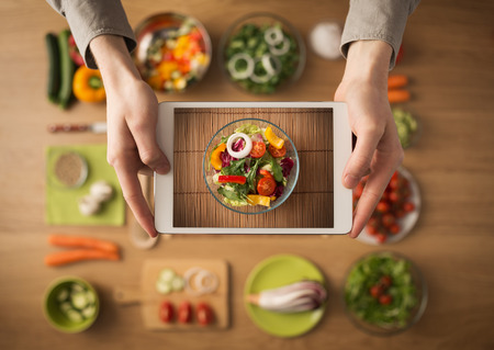 food ingredient: Hands holding a digital touch screen tablet with fresh vegetables and kitchen utensils  Stock Photo