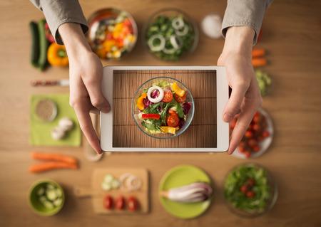 plato de comida: Manos que sostienen una tableta de pantalla t�ctil digital con verduras frescas y utensilios de cocina