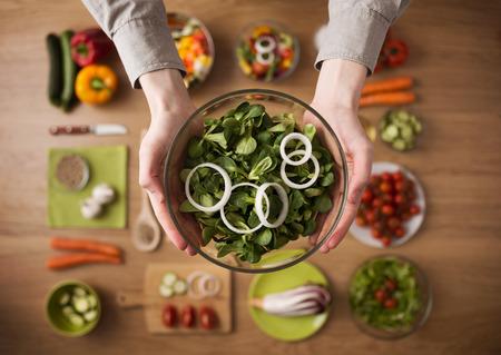 an onions: Manos que sostienen una ensalada vegetariana fresca saludable en un cuenco, verduras crudas frescas