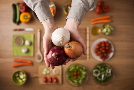 Hands holding different types of onions with fresh raw vegetables and salad bowls Banque d'images