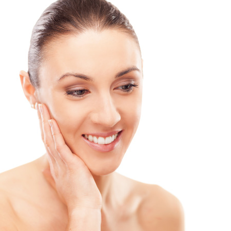 beauty treatment: Beautiful young woman touching her radiant face skin, spa beauty treatment concept