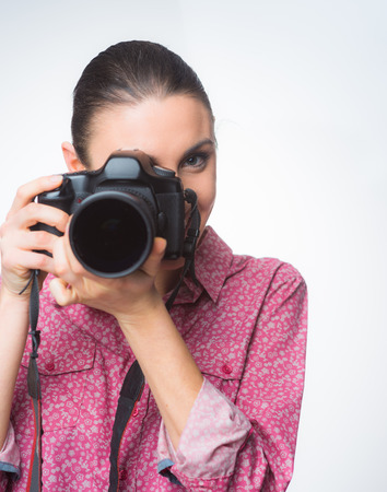 photo shooting: Female photographer shooting with a dslr camera on white background