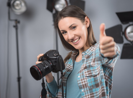 lighting equipment: Young female photographer posing in her professional studio, holding a digital camera with lighting equipment