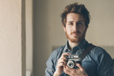 photojournalist: Vintage photographer portrait, he is holding an old camera and posing