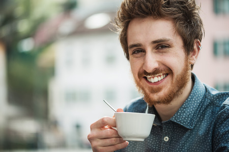 inattentive: Funny cheerful guy having a cappuccino at the bar with milk moustache, smiling at camera