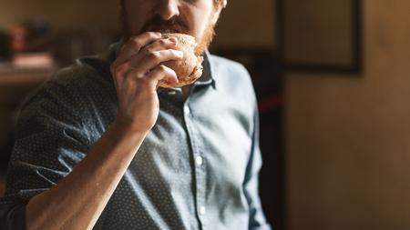 bocadillo: Joven hambriento comer un sabroso sándwich con jamón, cerrar la mano hacia arriba