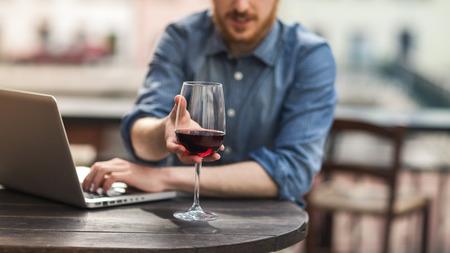 tomando vino: Joven sentado en la mesa de bar al aire libre con una copa de vino tinto y el uso de su computadora portátil Foto de archivo
