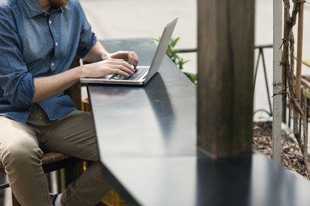 Unrecognizable man using a modern portable computer on an outdoor table, street on background Stock Photo