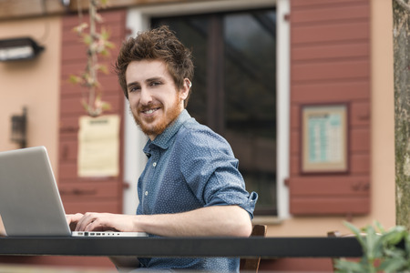 rolledup sleeves: Smiling  young man working on a laptop on a bar outdoor table