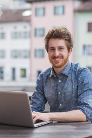 Smiling  young man working on a laptop on a bar outdoor table