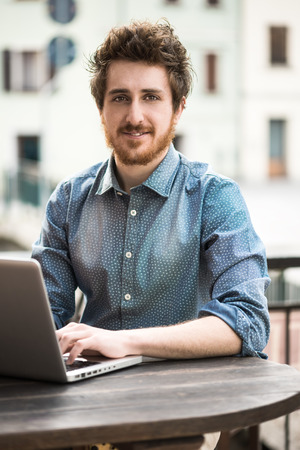 Smiling  young man working on laptop on a bar outdoor table Stock Photo