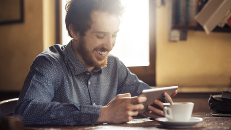 using tablet: Cheerful man  enjoying and social networking with his tablet during a coffee break