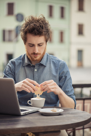 adding sugar: Young man having a coffee break at the bar and using a laptop, he is adding sugar in his cappuccino Stock Photo