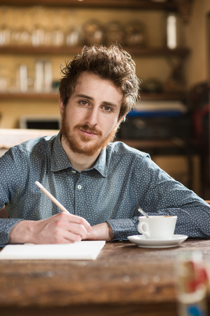 creative writer: Young man drawing on his sketchbook and having a coffee break, he is smiling at camera
