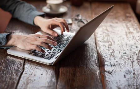 Man aan het werk op een laptop op een rustieke houten tafel, handen close up
