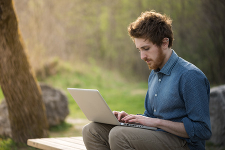 outdoor: Young  man working with his laptop outdoors in nature, trees and plants on background Stock Photo