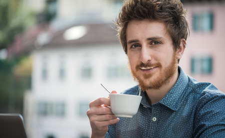 drink coffee: Funny cheerful guy having a cappuccino at the bar with milk moustache, smiling at camera