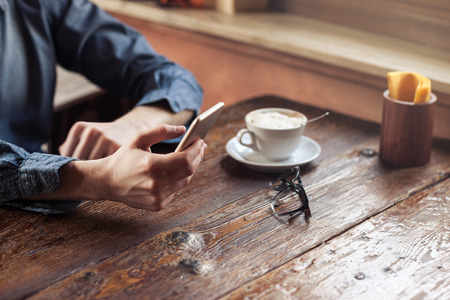 landline: Young hipster guy texting with his mobile phone at the bar and having a cappuccino