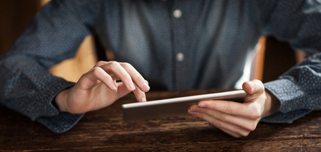 Young man using a digital touch screen tablet on a wooden table, hands close up