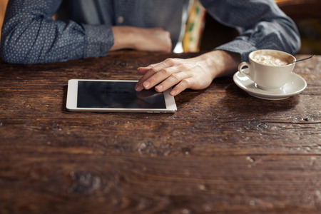 unrecognizable person: Young man having a coffee break and using a digital tablet on a rustic wooden table, unrecognizable person, hands close up