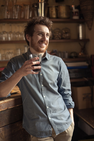 enjoyment: Hipster young smiling man drinking a glass of drink and leaning on a wooden table